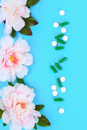 Capsules, pills and tablets with flowers on a blue table background. Top view, flat lay