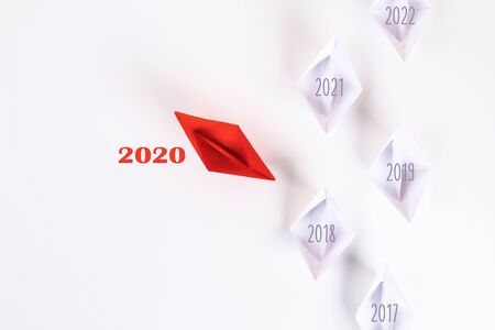 The new year 2020 is floating away from a succession of years 2018, 2019, 2021, 2022. Red paper boat among other white. Origami. Top view, flat lay, copy space. Zdjęcie Seryjne