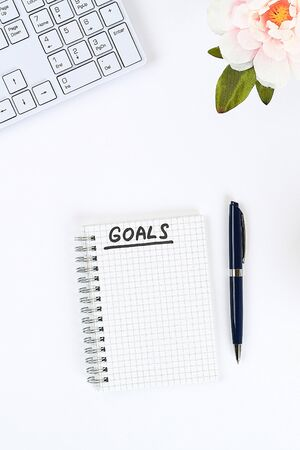 Write a goal for the new year 2020 in a white notebook on a white desktop next to a coffee mug and a keyboard. Top view, flat layout Zdjęcie Seryjne