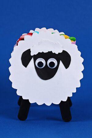 Diy Eid al adha lamb sheep sweet candy paper, wooden sticks for ice cream on blue background. Gift idea, decor Eid al adha. Process kid children craft. Workshop.