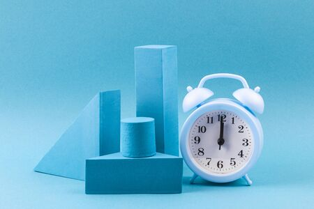 Blue geometric shapes with an alarm clock on a blue background. Template composition for advertising, products. Archivio Fotografico