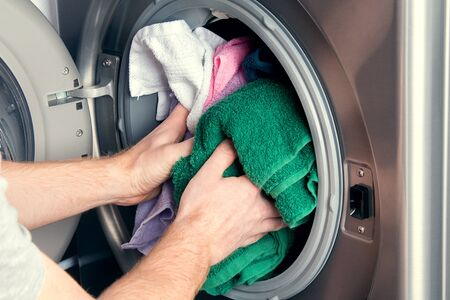 Man taking color clothes from washing machine. A drum of washing machine full of dirty laundry in bathroom.