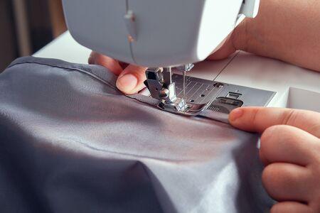 A man hem a curtain on sewing machine. Sewing, hobbies, hobby, home improvement.