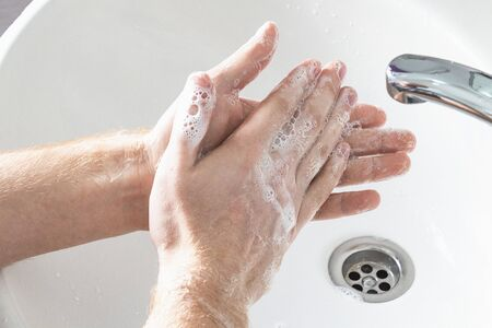 Man use soap and washing hands under water tap. Hygiene concept hand detail.