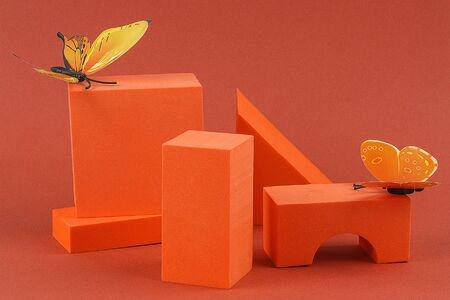 Orange geometric shapes with butterflies on a brown background. Template composition for advertising, products.