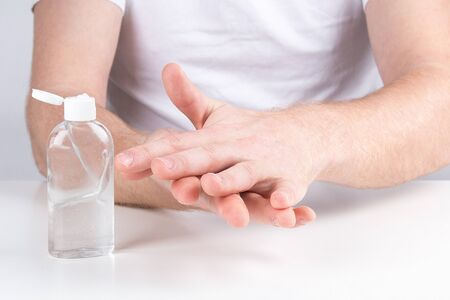 Man person using small portable antibacterial hand sanitizer on the hands.