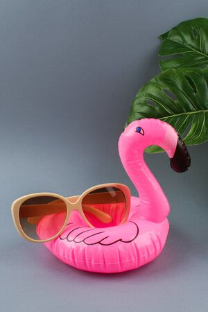 Pink inflatable flamingo on a gray background with sunglasses and monstera leaves. Summer concept of vacation. Background for sale. Archivio Fotografico