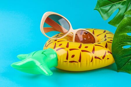 Inflatable pineapple on a blue background with sunglasses and monstera leaves. Summer concept of vacation. Background for sale.