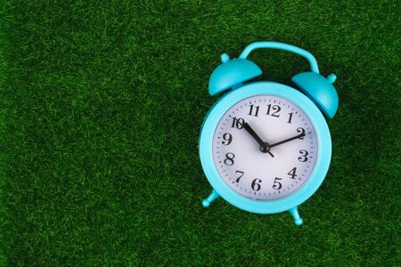 Alarm clock on grass or lawn background - time concept. Blue alarm clock with fresh green grass.