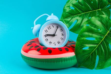 Inflatable watermelon on a blue background with monstera leaves and clock. Summer concept of vacation. Background for sale. Archivio Fotografico