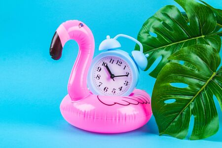 Pink inflatable flamingo on a blue background with monstera leaves and clock. Summer concept of vacation. Background for sale.