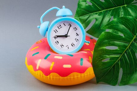 Inflatable donut on a grey background with monstera leaves and clock. Summer concept of vacation. Background for sale.
