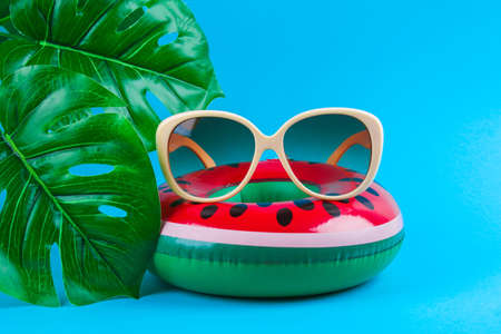 Inflatable watermelon on a blue background with sunglasses and monstera leaves. Summer concept of vacation. Background for sale. Archivio Fotografico