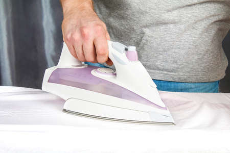 A man strokes linen with an black electric iron on an ironing board. Household.