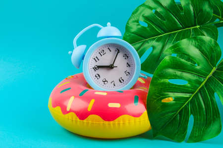 Inflatable donut on a blue background with monstera leaves and clock. Summer concept of vacation. Background for sale. Archivio Fotografico