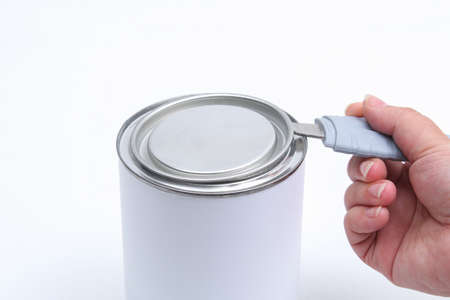 A man opens a jar of white paint with a can opener on a white background. Renovation concept.
