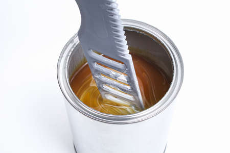 A man stirring white paint in a can on a white background. Renovation concept. Stock Photo