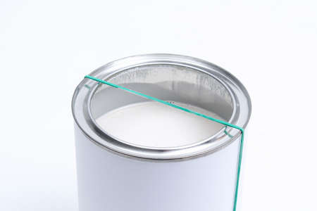 A man removes excess paint from a brush in a can on a white background. Renovation concept.