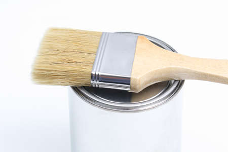 The brush lies on a can of white paint on a white background. Renovation concept.