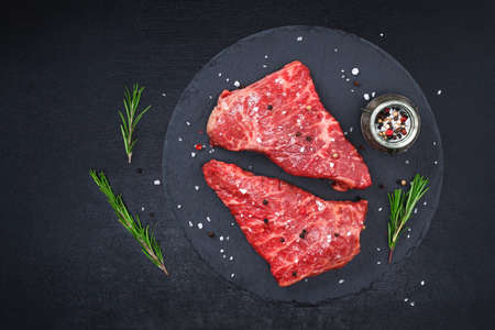 Raw steak on a cutting board with rosemary and spices, dark black background, top view. Fresh grilled meat. Grilled beef steak.