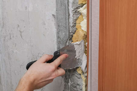 The man is plastering the walls in the room. Close-up. Stock fotó