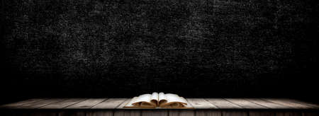 Old books open on wood and black walls