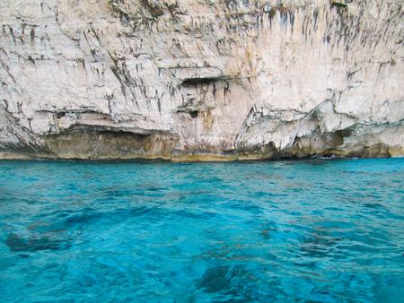 rockwall: Bright rockwall, bright blue water Stock Photo