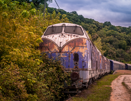 Beautiful vintage blue train abandoned by the woods