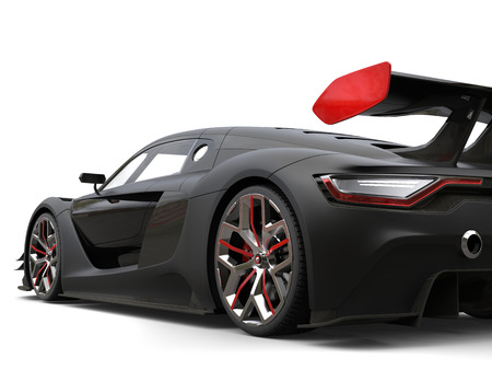 Gorgeous matte black super car with red details on the wheels and rear wing