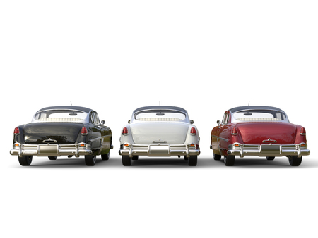 restored: Striking vintage cars - black, white and cherry red - back view Stock Photo