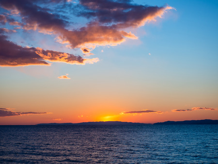 Beautiful sunset over cool blue sea - islands and mountains on the horizon 版權商用圖片