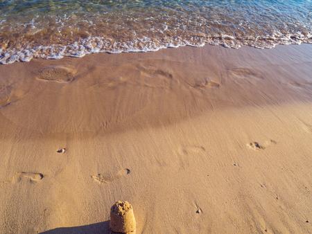 Footprints and small sand castle on the empty beach - calm small waves Reklamní fotografie