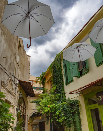 Back street of Mediterranean town with amazing street decorations and big vines climbing the buildings - Crete, Greece
