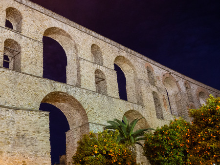 Ancient Roman aqueduct, orange trees and palms in front of it - night shot - Kavala, Greece