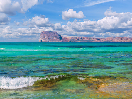Amazing crystal clear blue water on a paradise beach - small wave - rocky island in the background Reklamní fotografie