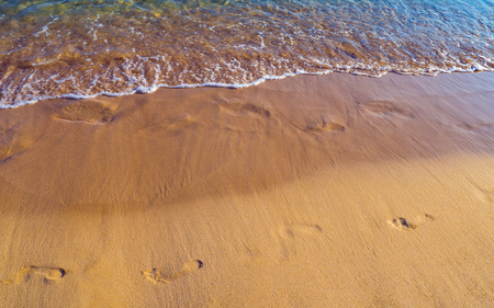 Footprints in the sand on the empty sandy beach - small foamy wave and clear blue water Reklamní fotografie