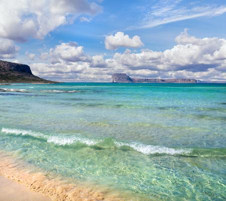 Amazing Mediterranean beach, clear blue calm sea, island in the background and beautiful sky