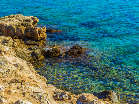 Amazing crystal clear blue water and sharp rock edges on the shore
