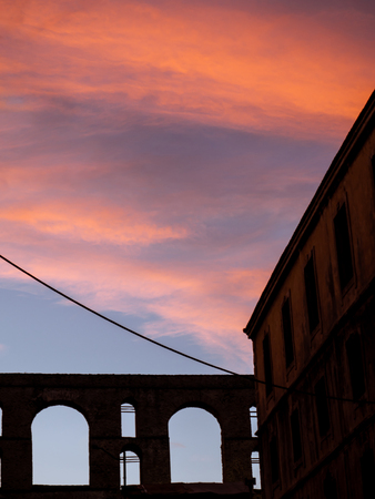 Sunset clouds in the old part of town - abandoned building and ancient Roman aqueduct in the background Stock fotó