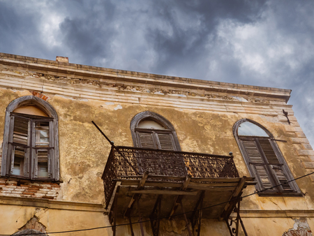 Very old Mediterranean abandoned building with beautiful balcony and wooden windows - rustic beauty