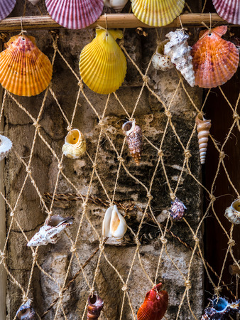 Rope net homemade decoration with small colorful sea shells tied to it