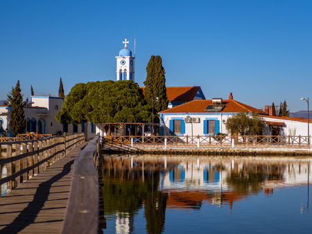 Small Greek Orthodox church on a small lake island with a narrow wooden bridge leading to it