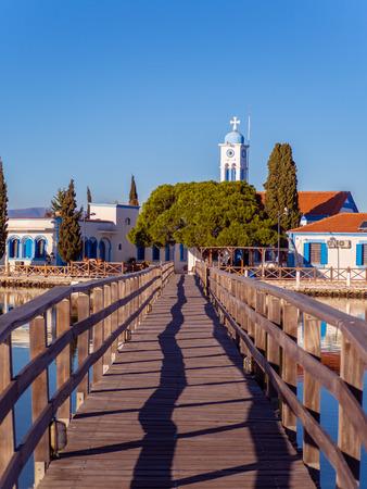 Narrow wooden bridge leading to the small Greek Orthodox church Reklamní fotografie