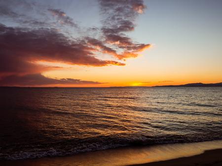 Sun set over the horizon - beautiful empty beach - small waves 版權商用圖片