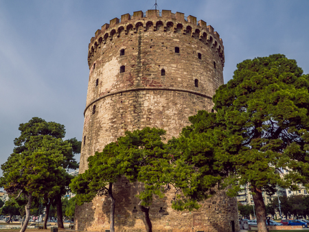 White Tower of Thessaloniki - medieval prison tower, now a museum, surrounded by trees - Thessaloniki, Greece