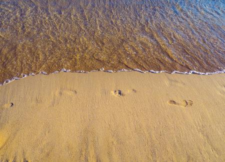 Footprints in the sand on a  empty sandy beach, calm sea