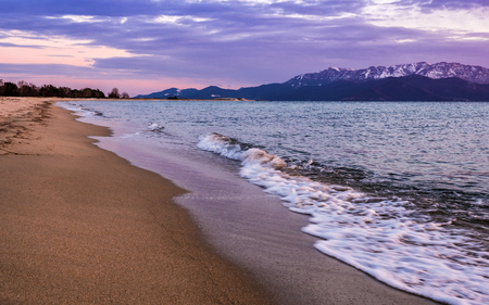 Empty beach in the evening - waves crashing on the sand