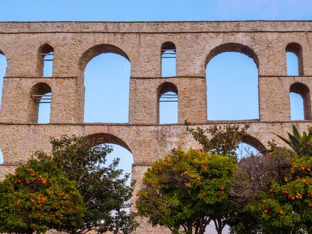 Ancient Roman aqueduct in Greece with orange trees in front of it Stock Photo
