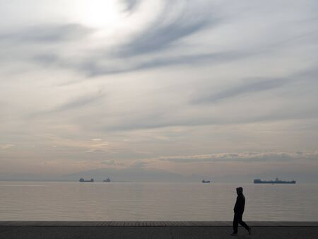A guy in a hoodie walking near the docks - cloudy weather
