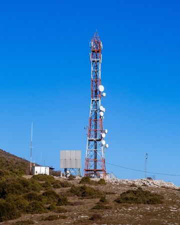 Big red and white antenna tower on top of the mountain Imagens